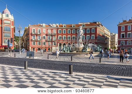 NICE, FRANCE - OCTOBER 2, 2014: View of Place Massena with Fountain of the Sun (Fontaine du Soleil) surrounded by red buildings of italian architecture.