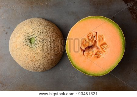 Two halves of the same cantaloupe, the cut side is showing the pulp and seeds, the other half is rind side up. Overhead view in horizontal format.