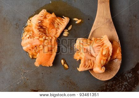 High angle shot of the scooped out seeds and flesh of a cantaloupe with a wooden spoon and the seed pulp. Overhead view in horizontal format.