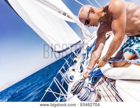 Handsome shirtless sailor working on sailboat, pulling rope on crank, summer time activity, spending vacation in a sea traveling