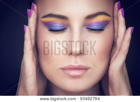 Closeup portrait of a beautiful woman face with colorful stylish makeup over dark background, model with closed eyes showing purple and yellow eyeshadow, beauty and fashion