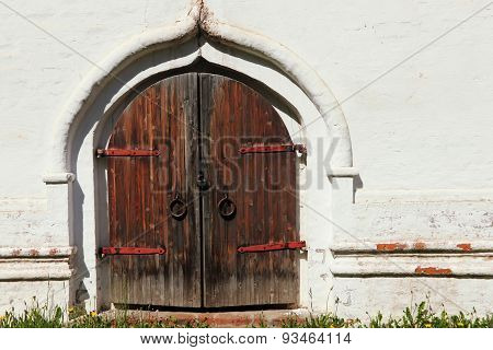 Old Castle Wooden Gate And White Wall.