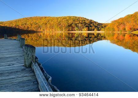 Mountain Lake with Dock Surrounded by Autumn Trees