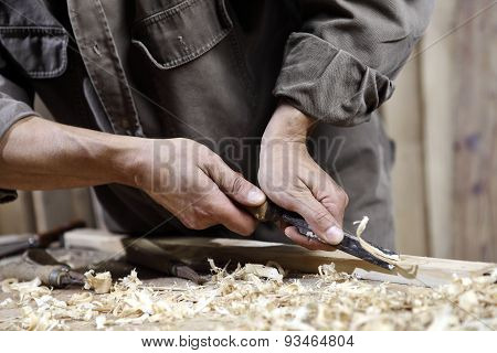 Carpenter With Chisel In The Hands On The Workbench In Carpentry