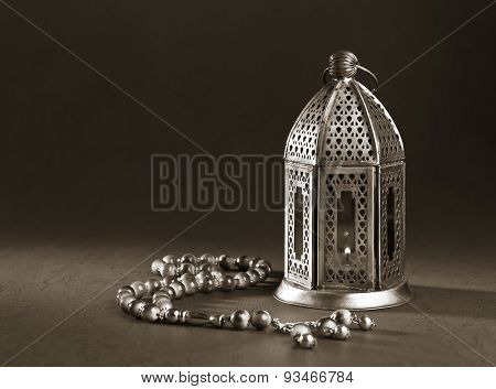 A metallic Ramadan lamp with Islamic rosary beads on black background. Monochromatic image.