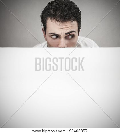 Man hiding behind a white cardboard