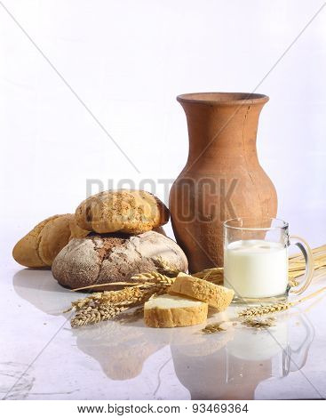 Milk In A Transparent Mug And Fresh Bread On A White Background