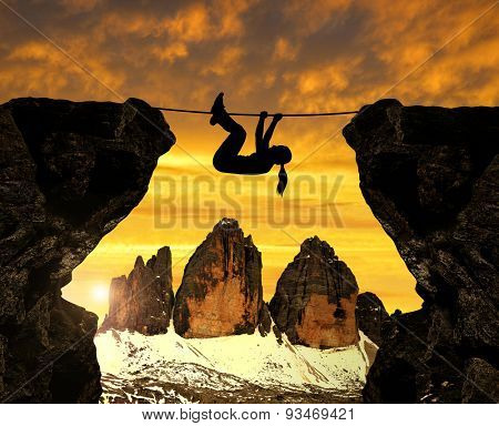Silhouette girl climbs on a rope over an abyss. In the background Tre Cime di Lavaredo - Dolomites , Italy