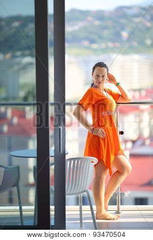 Beautiful woman in an orange dress standing on the terrace in the room
