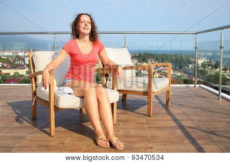 Beautiful young woman in a red shirt sitting in a chair on the terrace