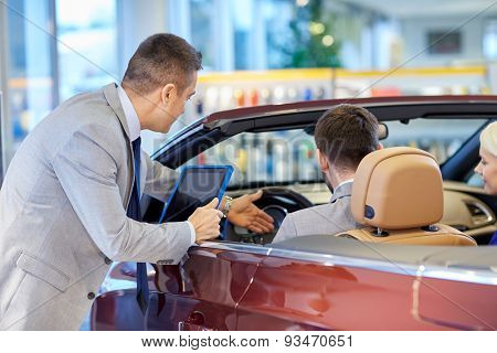 auto business, car sale, consumerism and people concept - happy couple sitting in cabriolet with car dealer in auto show or salon