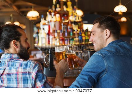 people, leisure, friendship, communication and bachelor party concept - happy male friends drinking beer and talking at bar or pub from back