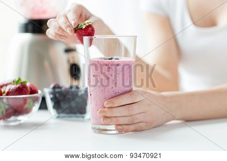 healthy eating, cooking, vegetarian food, dieting and people concept - close up of woman hands decorating milkshake with strawberry at home