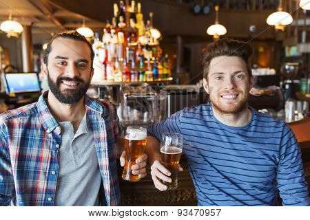people, leisure, friendship and bachelor party concept - happy male friends drinking beer and talking at bar or pub
