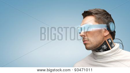 people, technology, future and progress - man with futuristic glasses and microchip implant or sensors over blue background