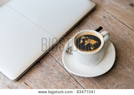 technology, business and modern life concept- close up of open laptop computer and coffee cup with world map silhouette on table at office or hotel room