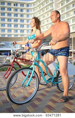 A man and a young woman in bathing suits on bikes on the hotel in the evening
