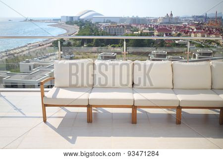 Seating area with beige sofa on the rooftop overlooking the city