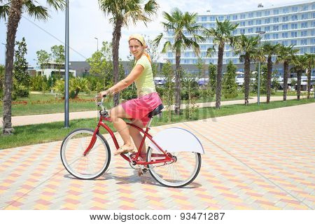 Young woman riding a red bicycle on beautiful area of hotel