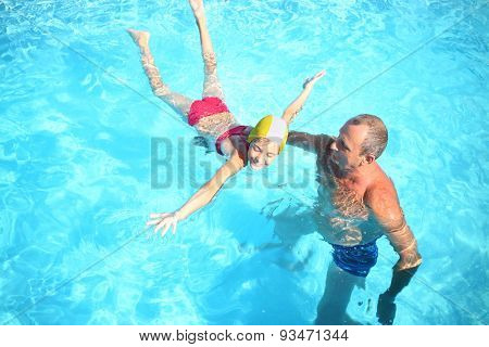 Grandpa teaches granddaughter to swim in the swimming pool, view from the top