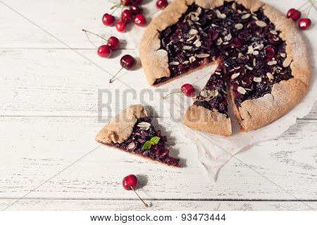 Homemade sea biscuit with cherries on white wooden background. Summer still life.