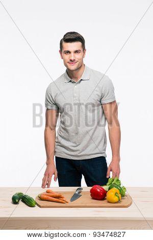 Happy man preparing salad over gray background