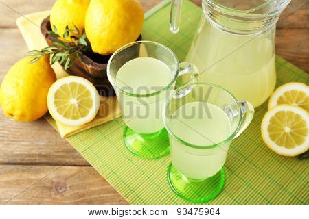 Still life with lemon juice and sliced lemons on color mat, closeup