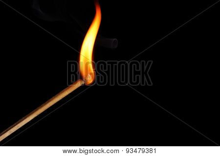 Burning match on dark background