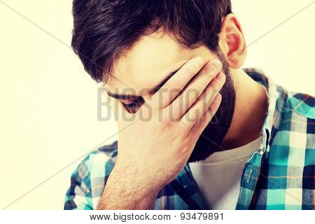 Young upset man covering his face.