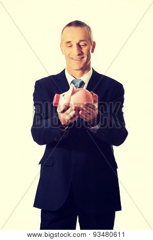 Smiling mature businessman holding piggybank.