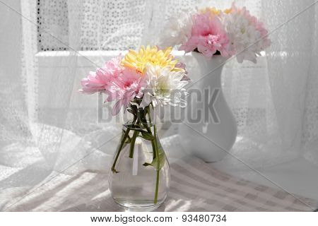 Beautiful chrysanthemums in vases on fabric background