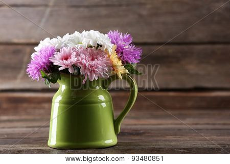 Beautiful chrysanthemums in pitcher on wooden background