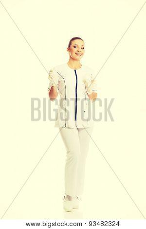 Full length female nurse holding a drip.