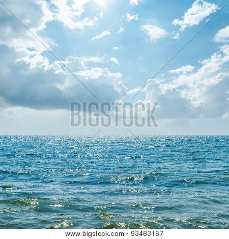 blue sea with sun in clouds