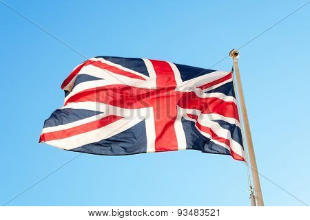 British flag or union jack flying on a flag pole against a blue sky
