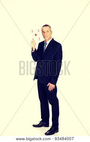 Mature elegant business man with red ace card.