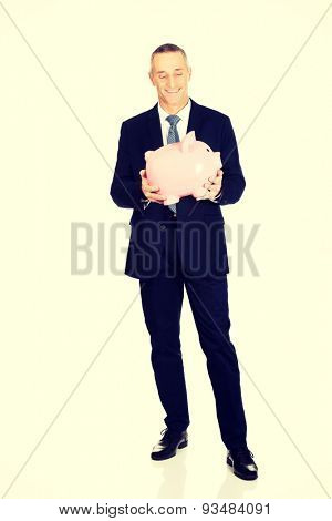 Full length cheerful businessman holding piggybank.