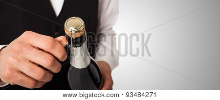 Portrait of a waiter holding a champagne bottle, celebration concept