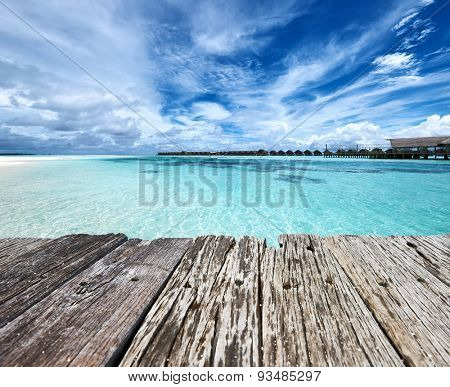 Beautiful beach and old wooden pier with water bungalows at Maldives