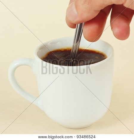 Hand mixing with a spoon of prepared coffee in cup