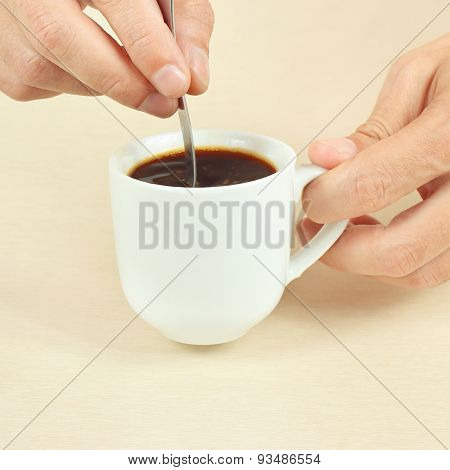 Hands mixing with spoon of black coffee in the cup