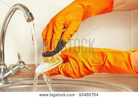 Hands in gloves with sponge wash the dirty plate under running water in kitchen