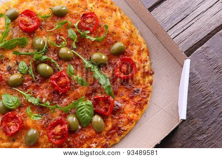 Pizza in box on wooden table, closeup