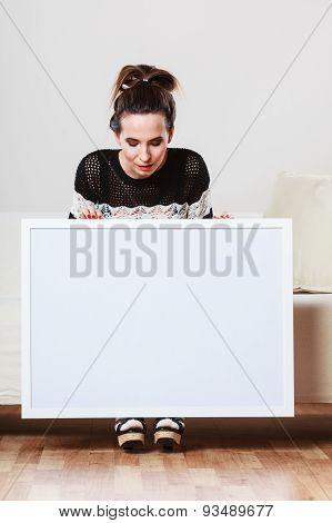 Woman On Sofa Holding Blank Presentation Board.