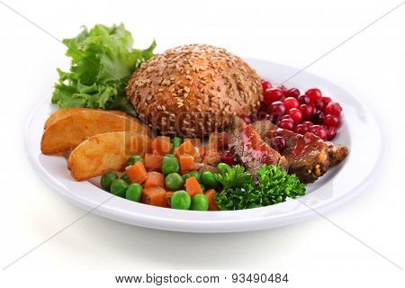 Beef with cranberry sauce, roasted potato slices, vegetables and bun on plate, isolated on white