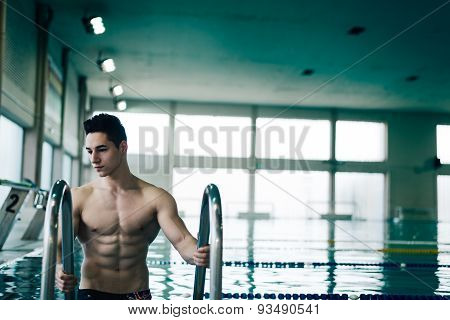 Muscular Swimmer On The Ladder