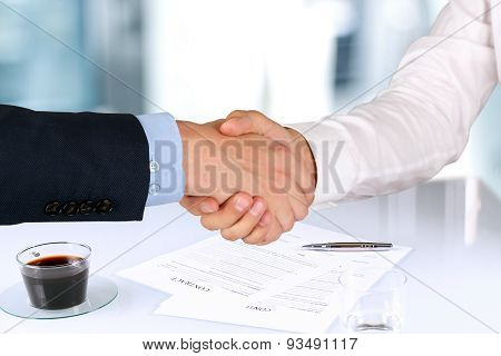 Close-up Image Of A Firm Handshake  Between Two Colleagues Under A Signing Contract