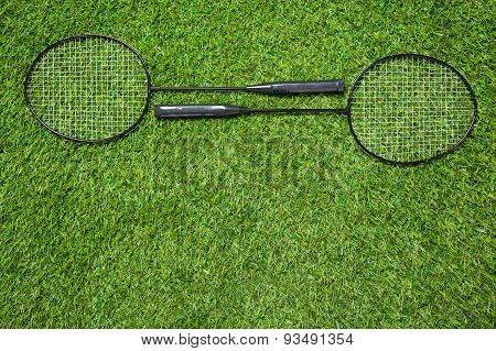 Two badminton rackets lying togeather on the grass