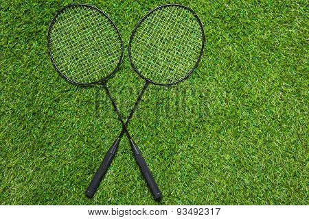 Two badminton rackets lying crossed on the grass