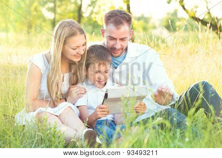 Happy Young Family with kid using Tablet PC in summer park. Dad, Mom and little boy with ipad computer resting outdoors together. Summer holidays